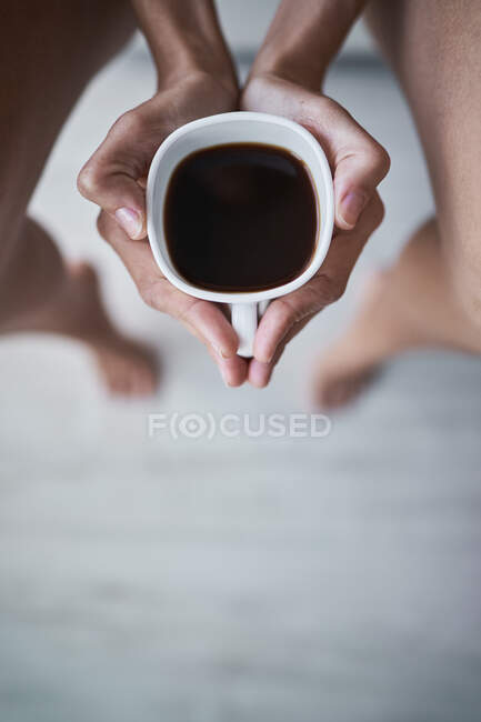 Top cropped view of woman holding cup of black coffee at home — Stock Photo