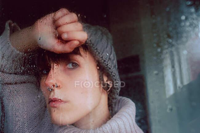Malheureux coûteux jeune femme en pull chaud et chapeau regardant loin par la fenêtre torride tout en passant la journée à la maison dans l'isolement de soi — Photo de stock