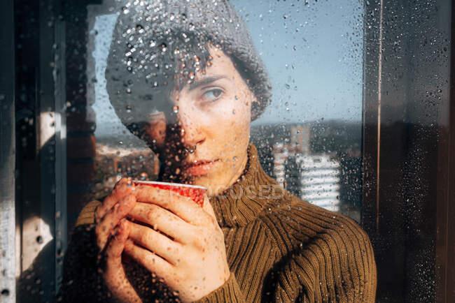 Jovem deprimida fêmea em suéter quente e chapéu de malha bebendo café e olhando através da janela molhada na cidade enquanto fica em casa durante a pandemia de coronavírus — Fotografia de Stock