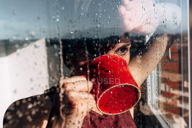 Mulher cuidadosa bebendo café perto da janela — Fotografia de Stock