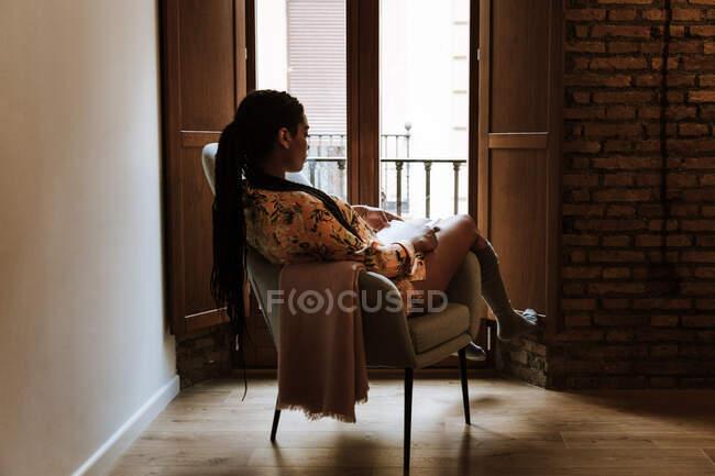 Donna etnica con libro a riposo a casa — Foto stock