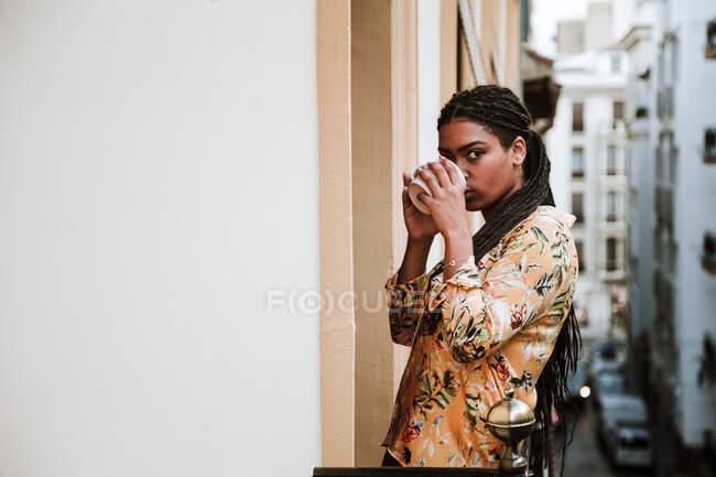 Jeune femme avec tasse de café debout sur le balcon — Photo de stock
