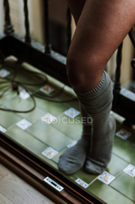 Desde arriba de la cosecha irreconocible mujer étnica en calcetines de rodilla acogedores de pie en el balcón mientras descansa en casa - foto de stock
