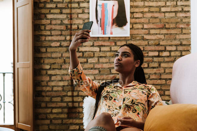 Joven mujer étnica tomando selfie en casa - foto de stock