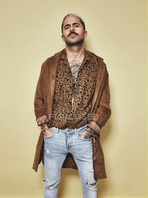 Дивна чоловіча модель з татуюваннями в модному пальто над сорочкою леопарда і джинсами, що стоять навпроти бежевого фону і дивляться на камеру. — стокове фото