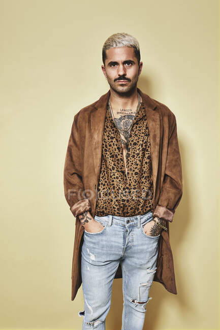 Fashionable male model with tattoos wearing trendy coat over leopard shirt and jeans standing against beige background and looking at camera — Stock Photo