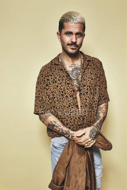 Fashionable male model with tattoos holding trendy coat over leopard shirt and jeans standing against beige background and looking at camera — Stock Photo