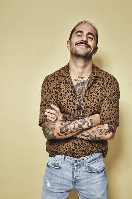 Cheerful fashionable male model with tattoos wearing trendy leopard shirt and jeans standing against beige background and looking at camera — Stock Photo