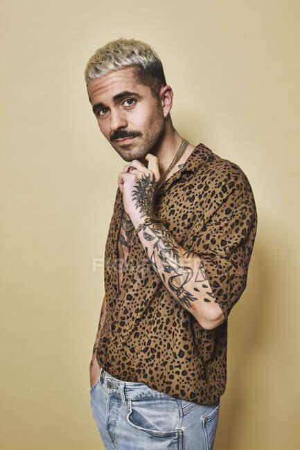 Modella maschile alla moda con tatuaggi che indossano camicia leopardata alla moda e jeans in piedi su sfondo beige e guardando la fotocamera — Foto stock
