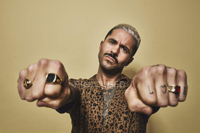 Provocative bearded guy in trendy outfit showing fists with tattoos and golden rings while standing against beige wall — Stock Photo
