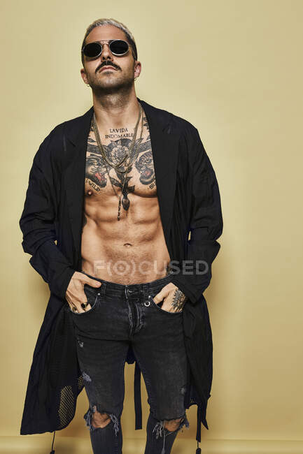 Brutal muscular male with tattooed torso wearing black coat and trendy ripped jeans with stylish sunglasses and accessories standing against beige background — Stock Photo
