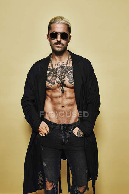 Brutal muscular sexy fit male with tattooed torso wearing black coat and trendy ripped jeans with stylish sunglasses and accessories standing against beige background — Stock Photo