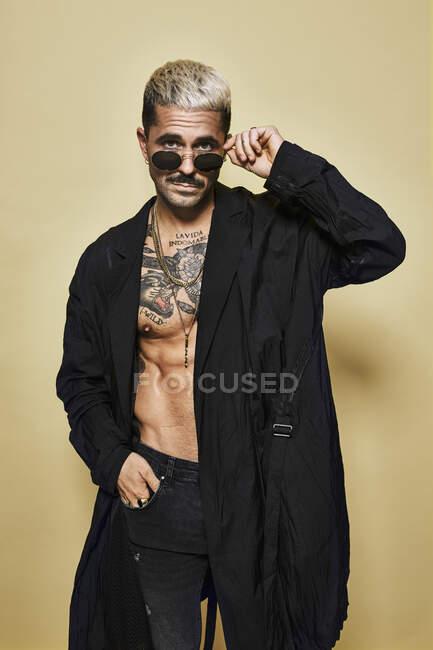 Brutal musclé sexy fit mâle avec torse tatoué portant manteau noir et jeans déchiré à la mode avec des lunettes de soleil élégantes et accessoires debout sur fond beige regardant la caméra — Photo de stock