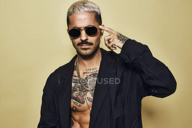 Portrait of brutal muscular sexy fit male with tattooed torso wearing black coat and stylish sunglasses and accessories standing against beige background looking at camera pointing finger to temple — Stock Photo