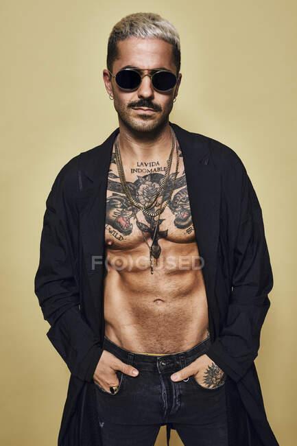 Brutal muscular sexy ajuste masculino con el torso tatuado con abrigo negro y vaqueros rasgados de moda con gafas de sol elegantes y accesorios de pie sobre fondo beige mirando a la cámara - foto de stock