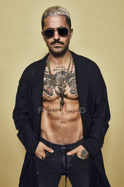 Brutal muscular sexy fit male with tattooed torso wearing black coat and trendy ripped jeans with stylish sunglasses and accessories standing against beige background looking at camera — Stock Photo