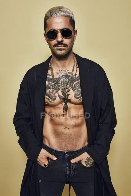 Brutale muscolare sexy fit maschile con busto tatuato indossando cappotto nero e jeans strappati alla moda con eleganti occhiali da sole e accessori in piedi sullo sfondo beige guardando la fotocamera — Foto stock