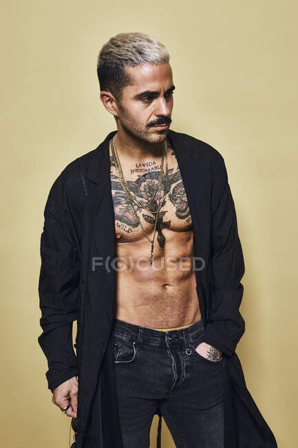 Brutal muscular sexy fit male with tattooed torso wearing black coat and trendy jeans with stylish sunglasses and accessories standing against beige background looking away — Stock Photo