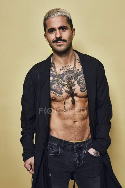 Brutal muscular sexy fit male with tattooed torso wearing black coat and trend and accessories standing against beige background looking at camera — Stock Photo