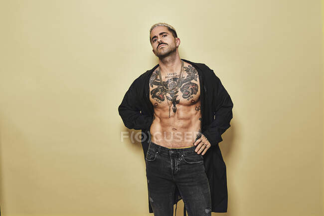 Confident arrogant stylish man with muscular tattooed torso wearing black coat and jeans looking at camera against beige background — Stock Photo
