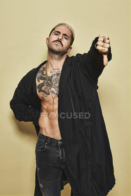 Young provocative male in black coat over naked tattooed torso showing thumbs down gesture in disapproval while standing against beige background — Stock Photo