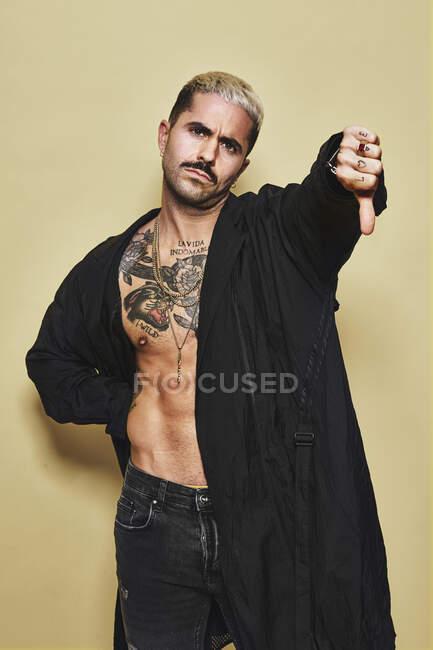Молодий провокативний самець у чорному пальто над голим татуйованим тулубом показує пальцями вниз жест несхвалення, стоячи навпроти бежевого фону. — стокове фото