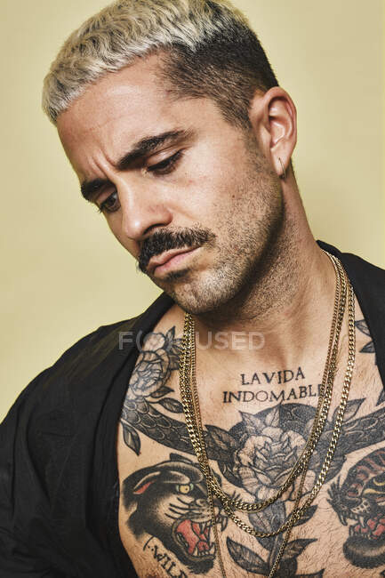 Confident arrogant stylish man with muscular tattooed torso wearing black coat looking away against beige background — Stock Photo