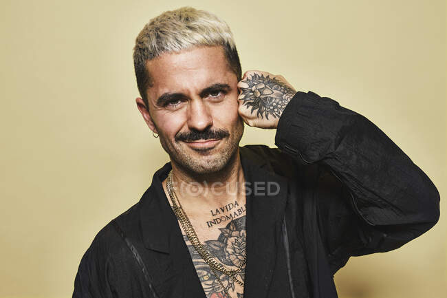 Portrait of unfriendly arrogant stylish man with muscular tattooed torso wearing black coat looking at camera against beige background making hand punch gesture to his temple — Stock Photo