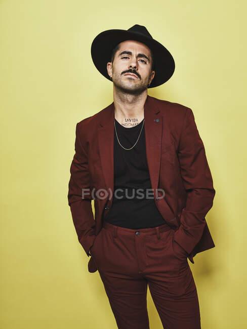 Guapo barbudo bien vestido macho en traje vinoso de moda y sombrero mirando a la cámara sobre fondo amarillo - foto de stock