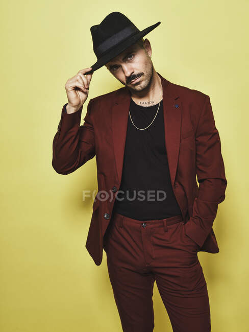 Handsome bearded well dressed male in trendy vinous suit and hat looking at camera against yellow background — Stock Photo