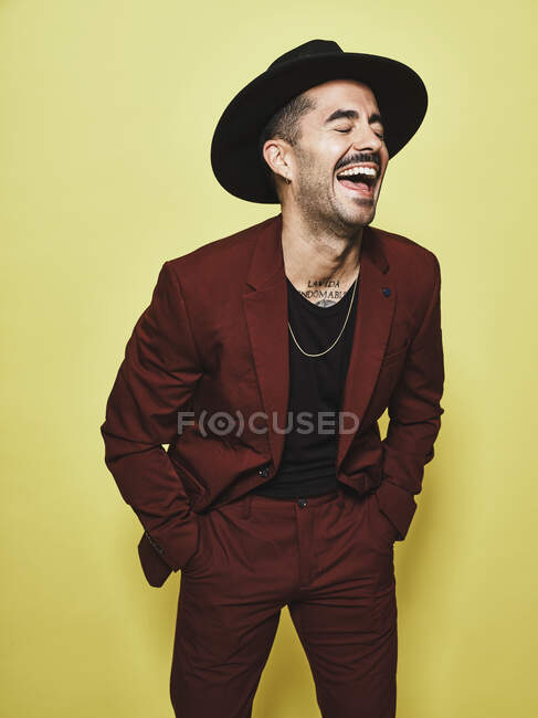 Ridendo maschio etnico adulto in abito alla moda vinoso e cappello con gli occhi chiusi in piedi contro lo sfondo giallo — Foto stock