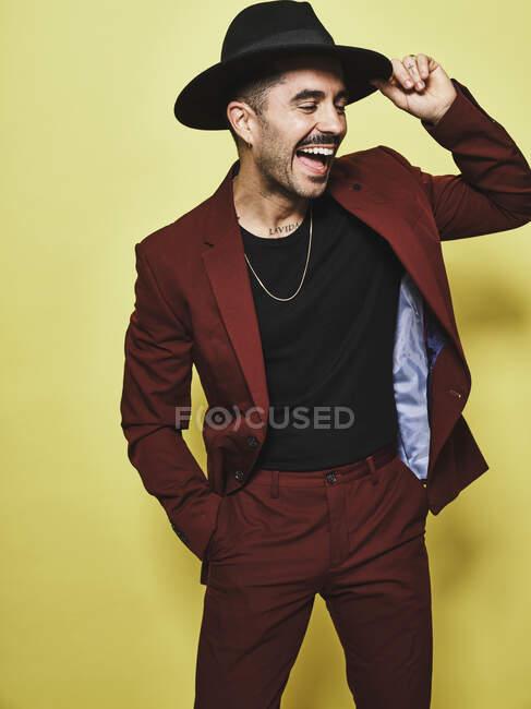 Rindo macho étnico adulto em terno vinoso na moda e chapéu de pé contra fundo amarelo — Fotografia de Stock