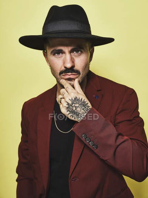 Graves tipo barbudo reflexivo en sombrero negro y traje de moda mantener los dedos cerca de la cara y mirando a la cámara contra el fondo amarillo - foto de stock