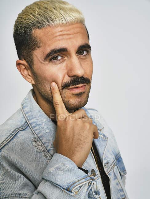 Портрет молодого етнічного чоловіка, який робить сірковину сумніваючись в обличчі пальцем, дивиться на камеру, одягнений в модний джинсовий піджак з квітковим візерунком, стоячи проти сірого фону — стокове фото