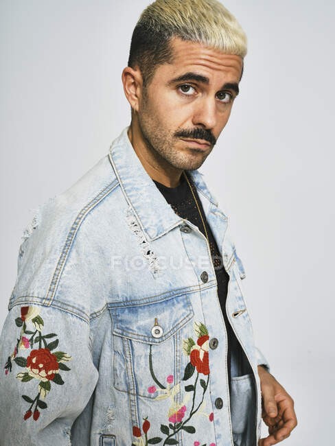Portrait of young ethnic looking at camera wearing trendy denim jacket with floral pattern while standing against gray background — Stock Photo