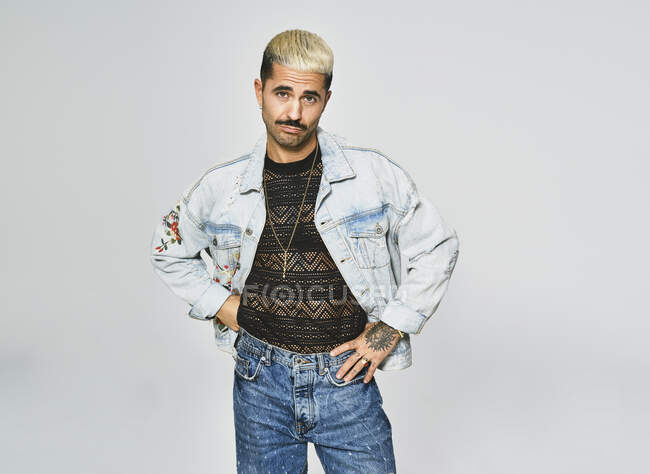 Young ethnic man making grimace doubting face looking at camera wearing trendy denim jacket with floral pattern while standing against gray background — Stock Photo