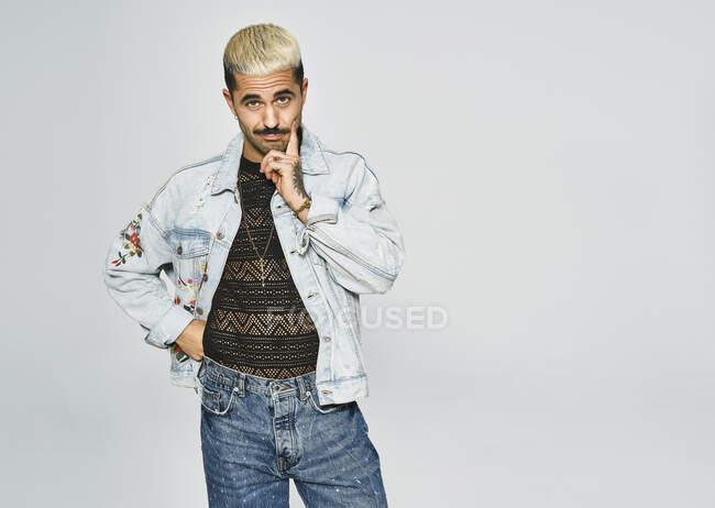 Молодий етнічний чоловік робить сірчані мімімізки сумніваючись в обличчі пальцем, дивлячись на камеру з модним джинсовим піджаком з квітковим візерунком, стоячи навпроти сірого фону. — стокове фото