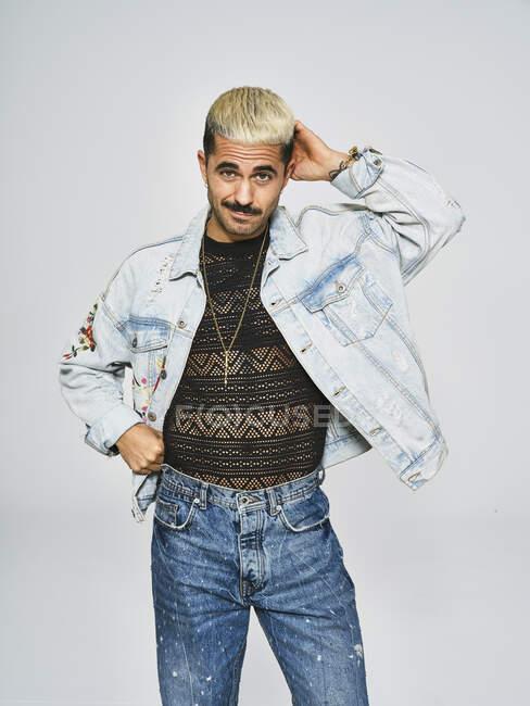 Giovane uomo etnico che fa faccia smorfia guardando la fotocamera indossa giacca di jeans alla moda con motivo floreale mentre in piedi su sfondo grigio — Foto stock