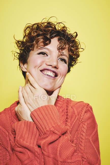 Stupito femmina allegra con i capelli ricci indossa maglione arancio maglia con le mani intorno al collo guardando altrove mentre in piedi contro lo sfondo giallo — Foto stock