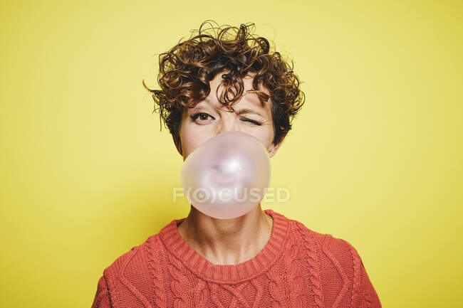 Young curly haired female in orange sweater blowing bubble gum and blinking looking to the camera while standing against yellow background — Stock Photo