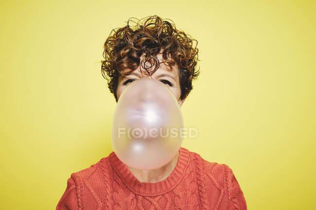 Joven hembra de pelo rizado en suéter naranja que sopla goma de mascar mirando a la cámara mientras está de pie sobre el fondo amarillo - foto de stock