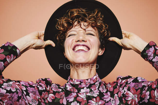Optimistic young beautiful female model with curly hair wearing stylish black hat and colorful blouse with closed eyes smiling while standing against orange background — Stock Photo