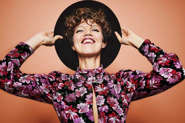 Ottimistico giovane bella modello femminile con i capelli ricci indossando elegante cappello nero e camicetta colorata guardando la fotocamera e sorridente mentre in piedi sullo sfondo arancione — Foto stock