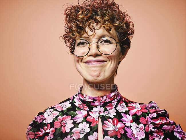 Happy young curly haired female in stylish floral blouse and trendy eyeglasses smiling and looking at camera against red background — Stock Photo