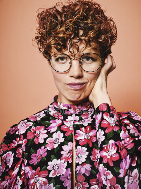 Thoughtful doubtful beautiful curly haired female in trendy eyeglasses and stylish colorful blouse with floral ornament looking at camera against pink background — Stock Photo