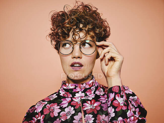 Thoughtful doubtful beautiful curly haired female in trendy eyeglasses and stylish colorful blouse with floral ornament looking away against pink background — Stock Photo