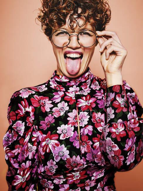 Bella femmina dai capelli ricci in occhiali alla moda ed elegante camicetta colorata con ornamento floreale guardando la fotocamera e facendo divertente smorfia con la lingua fuori in piedi contro lo sfondo rosa — Foto stock
