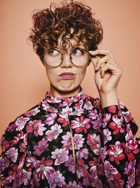 Pensée douteuse belle femme aux cheveux bouclés dans des lunettes à la mode et chemisier coloré élégant avec ornement floral regardant loin sur fond rose — Photo de stock