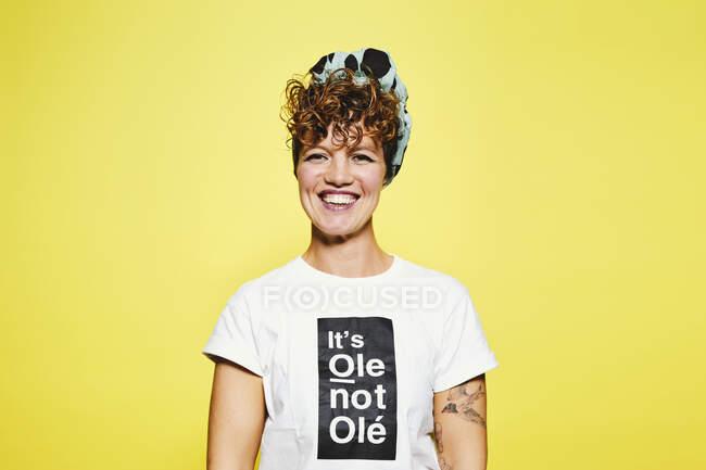 Erwachsene Frau im trendigen lässigen Outfit mit Kopftuch lächelt in die Kamera, während sie vor gelbem Hintergrund steht — Stockfoto