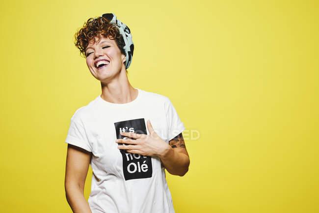 Donna adulta in abito casual alla moda con testa avvolgente con gli occhi chiusi e ridere ad alta voce a scherzo divertente mentre in piedi contro lo sfondo giallo — Foto stock